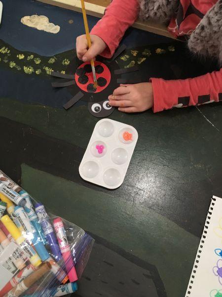 student painting ladybug